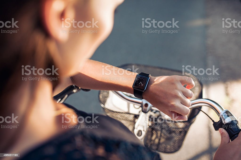 Woman with a bicycle looking at her smartwatch stock photo