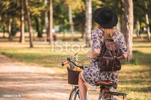 Woman with a bicycle riding in a park