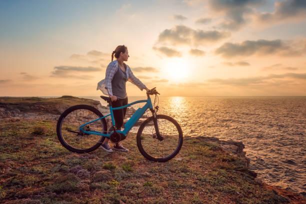 frau mit fahrrad in der natur - elektrorad stock-fotos und bilder