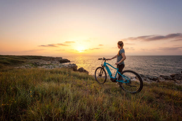 Woman with a bike in the nature Morning view of a woman with a bike enjoys the view of sunrise at the rocky Black Sea coast rocky coastline stock pictures, royalty-free photos & images