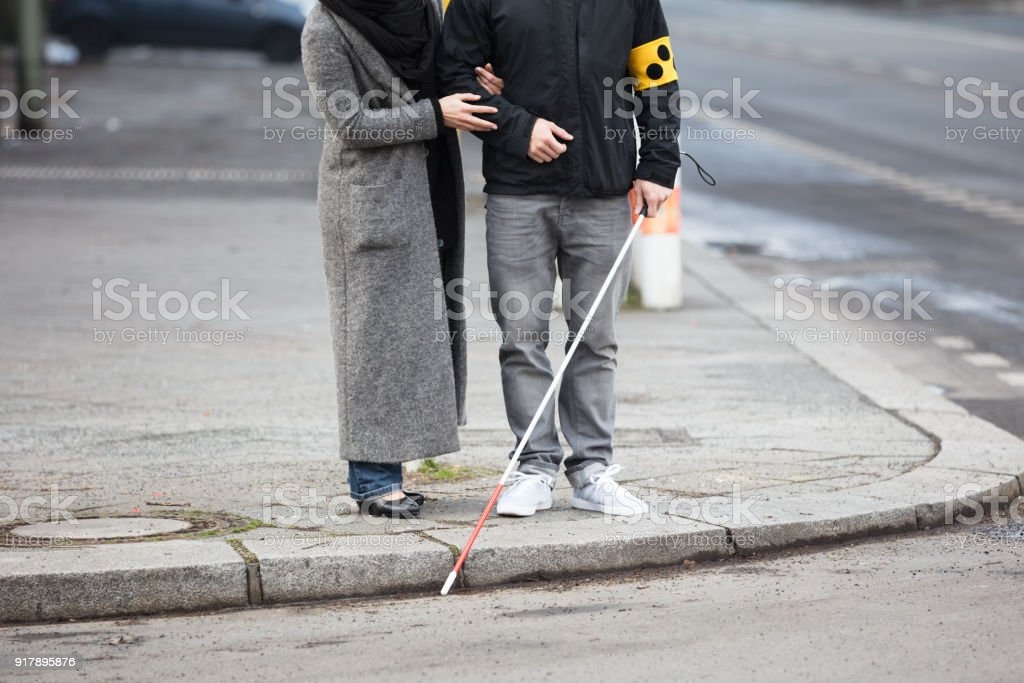 Woman With A Blind Man On Street stock photo