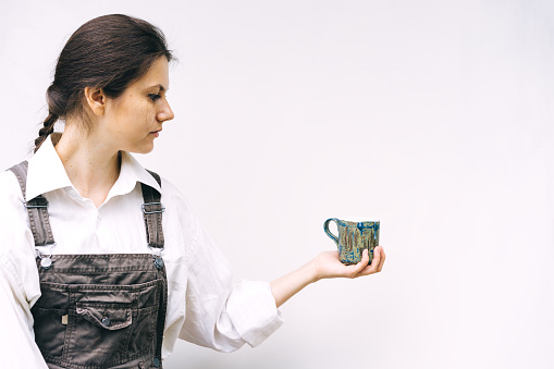 Woman with a blue ceramic mug in hand on a background of a white wall