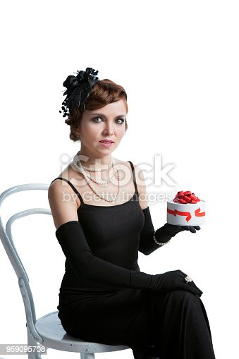 Young sexy woman in a long dress and a retro hat sits on a retro chair with a gift box of chocolates, waiting for guests