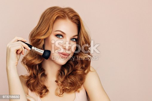 istock Woman with a brush for make-up powder 973258630