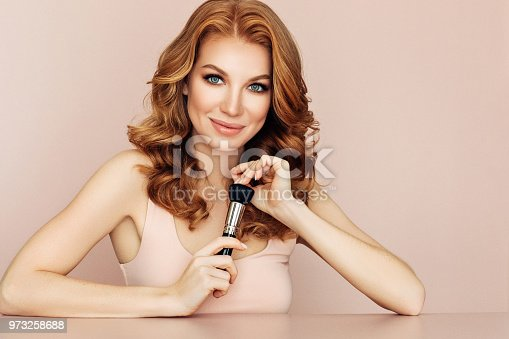 istock Woman with a brush for make-up powder 973258688