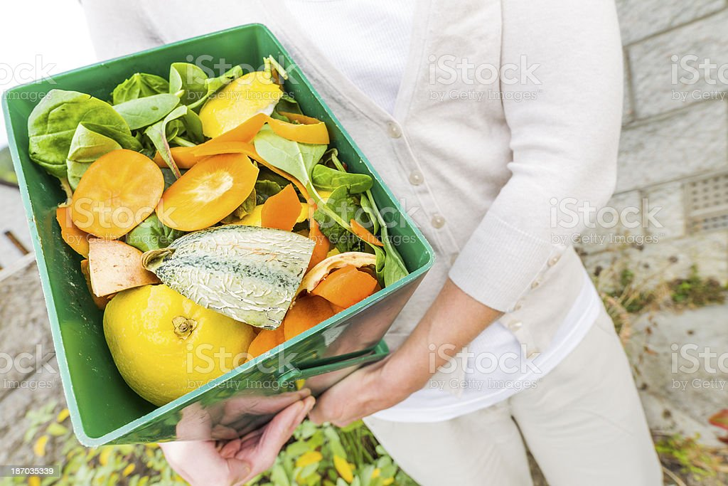A woman with a bucket of kitchen waste recycling stock photo