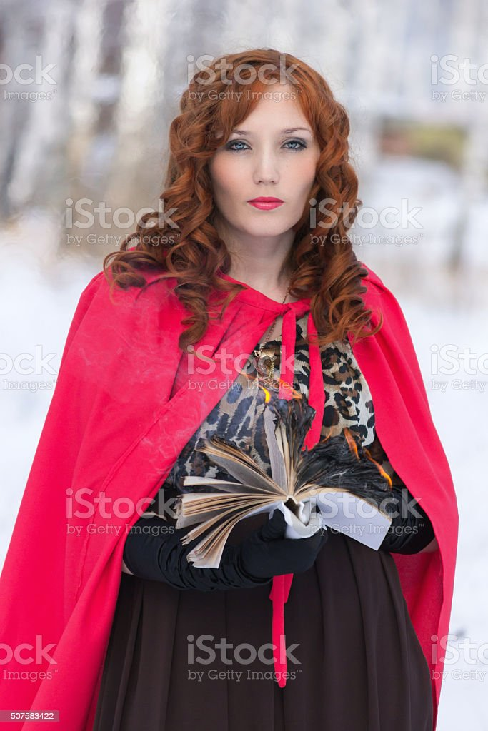 woman with a burning book in hand. Surrealism stock photo