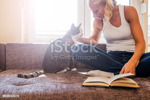 istock woman with a cat by the window reading a book / woman reading a book 863840074