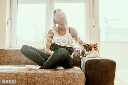 istock woman with a cat by the window reading a book / woman reading a book 863843132
