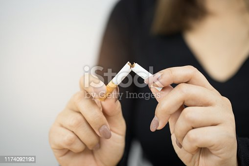 A photo of a black woman holding a cigarette