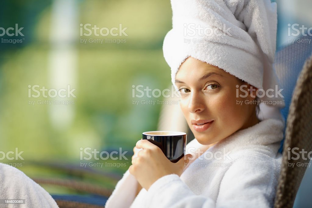 Woman with a coffee cup in white robe with hair in a towel royalty-free stock photo