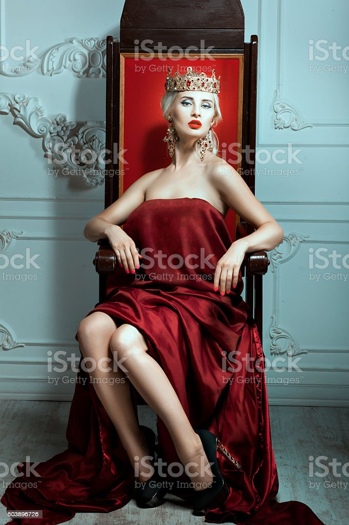 Woman with a crown his head sitting on the throne. stock photo