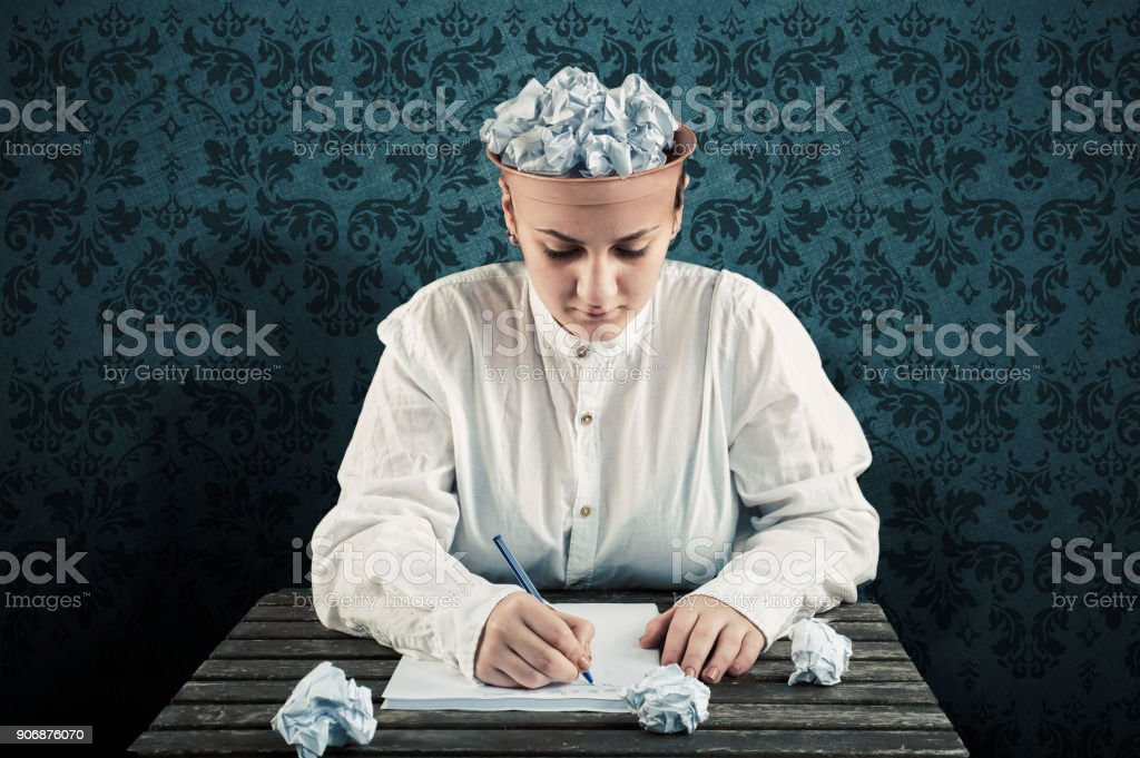 Woman with a crumpled paper in top of his head and writing on paper . stock photo