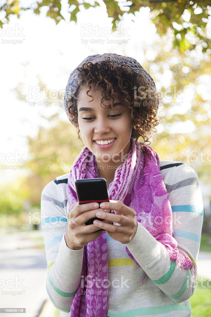 A woman with a curly hair wearing a pink scarf texting  royalty-free stock photo