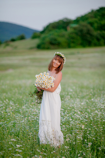 674214372 istock photo A woman with a daisies wreath on her head. 1207035221