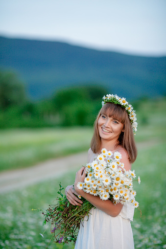 674214372 istock photo A woman with a daisies wreath on her head. 1207035238