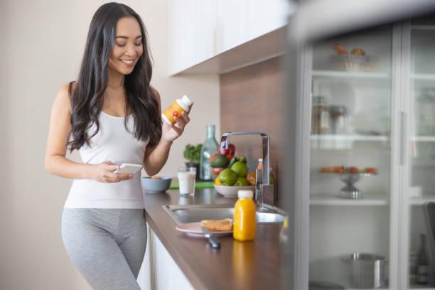 frau mit nahrungsergänzungsmittel in der küche - nahrungsergänzungsmittel stock-fotos und bilder