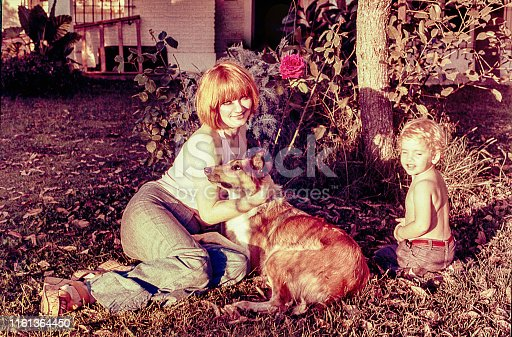 Vintage photo of a mother with her child sitting in the garden with a collie dog and looking at camera