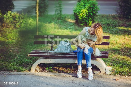 Young blond woman sitting on a bench with her pet dog in her lap