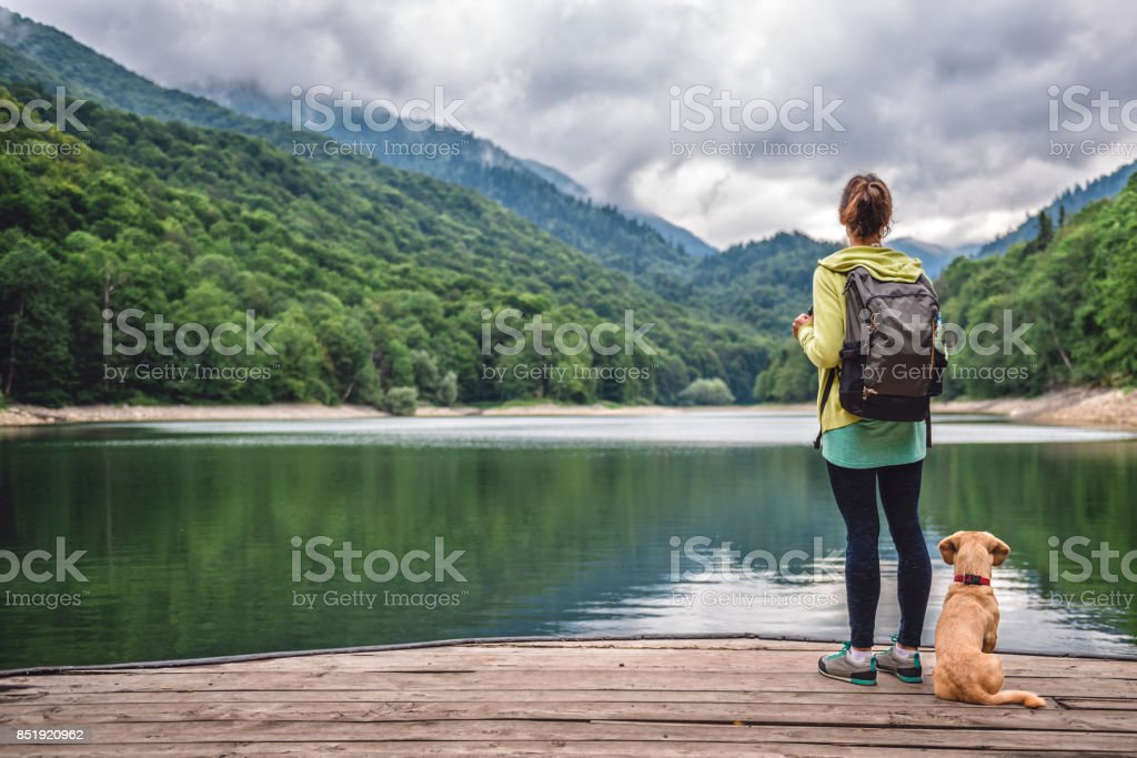 Woman with a dog standing on pier by the lake stock photo