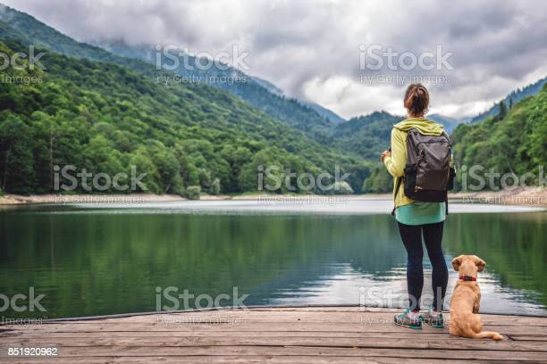 Photo of Woman with a dog standing on pier by the lake