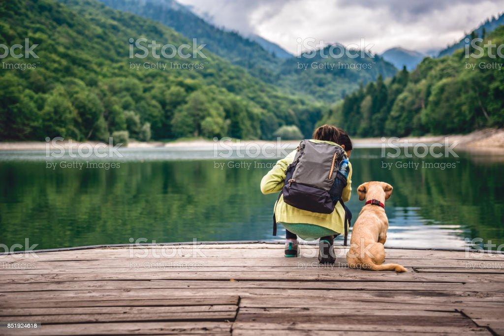 湖の桟橋で犬の地位を持つ女性 ストックフォト