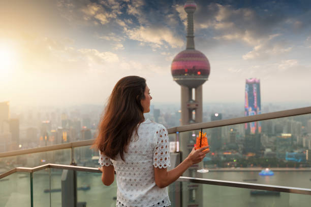 Woman with a drink in her hand enjoys the sunset over the skyline of Shanghai Elegant woman with a drink in her hand enjoys the sunset over the skyline of Shanghai, China pudong stock pictures, royalty-free photos & images