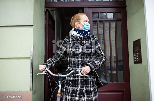 Woman wearing a face mask going out with her bicycle during corona virus outbreak. Female going out with a protective face mask.