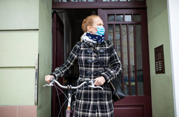 Frau mit einer Gesichtsmaske geht mit ihrem Fahrrad aus – Foto