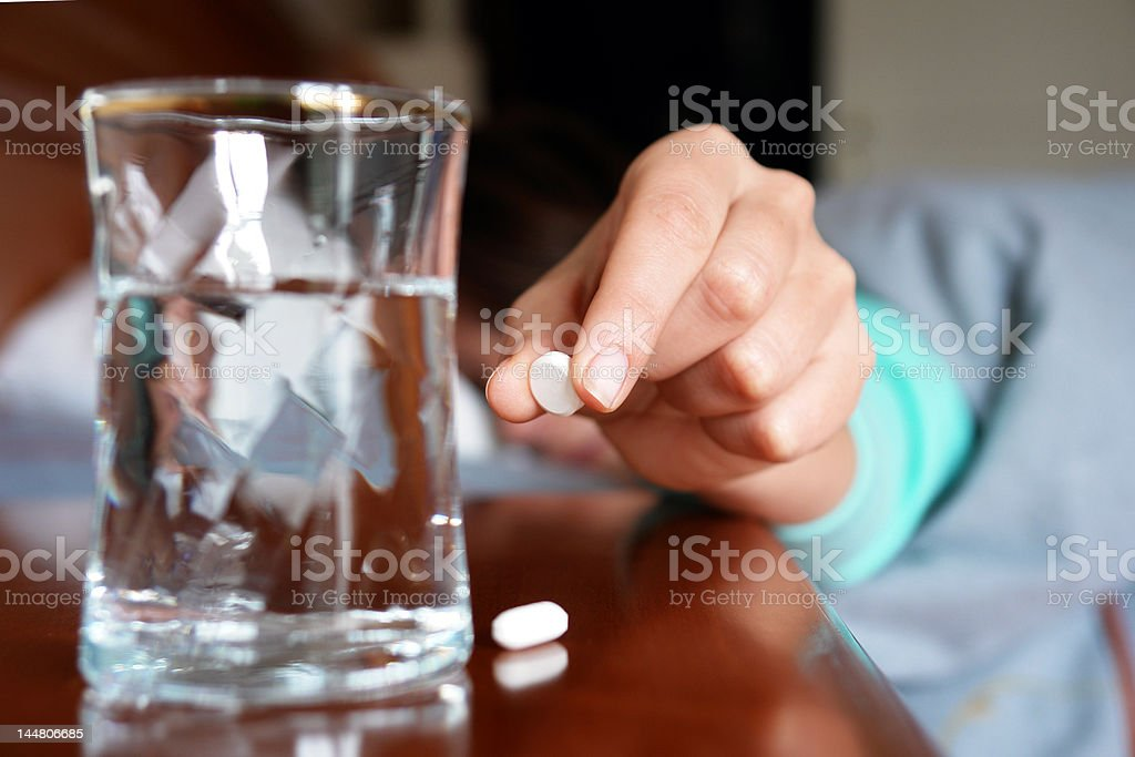 Woman with a flu taking pill stock photo