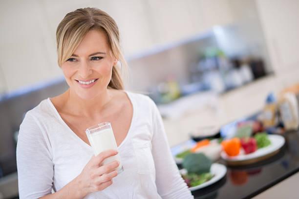 woman with a glass of milk - calcium stockfoto's en -beelden