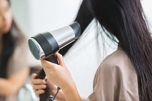 istock Woman with a hair dryer to heat the hair. 860904680
