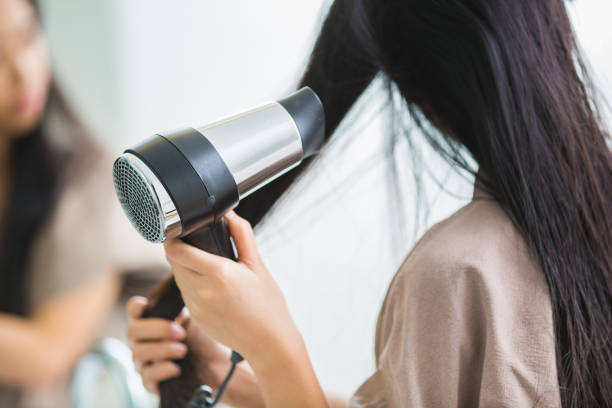 Woman with a hair dryer to heat the hair. stock photo