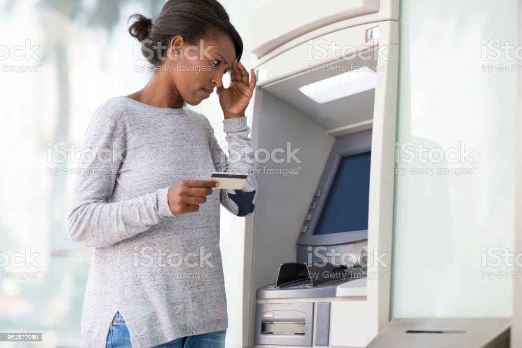 Woman with a headache holding hand on forehead, having financial problems to withdraw cash from an ATM machine. stock photo