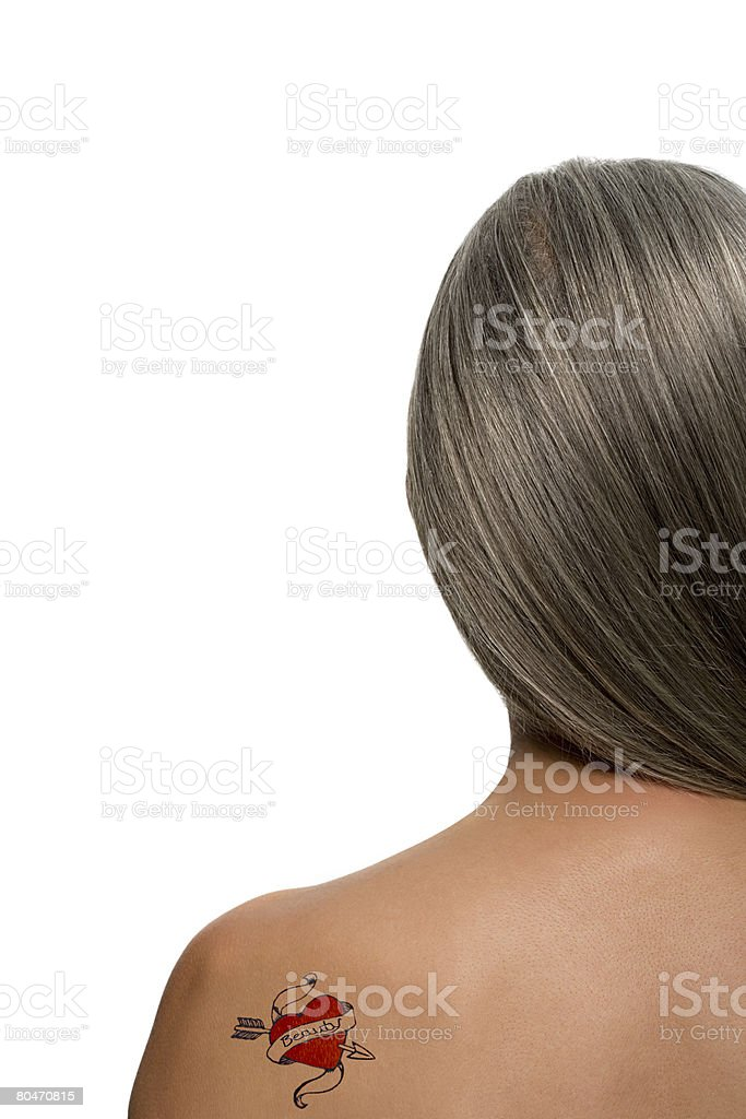 Woman with a heart shaped tattoo on her back stock photo
