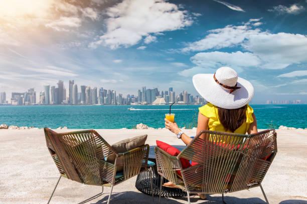 femme avec un jus à la main jouit de la vue à l'horizon de doha, qatar - qatar photos et images de collection