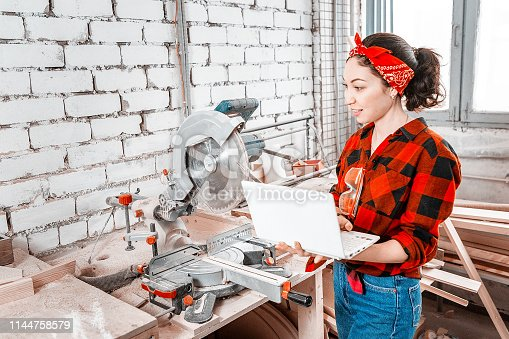 istock A woman with a laptop sets up with special software industrial machines with digital control in the workshop or in the factory 1144758579