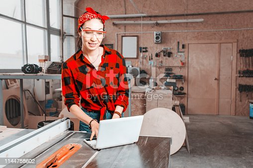 istock A woman with a laptop sets up with special software industrial machines with digital control in the workshop or in the factory 1144758602