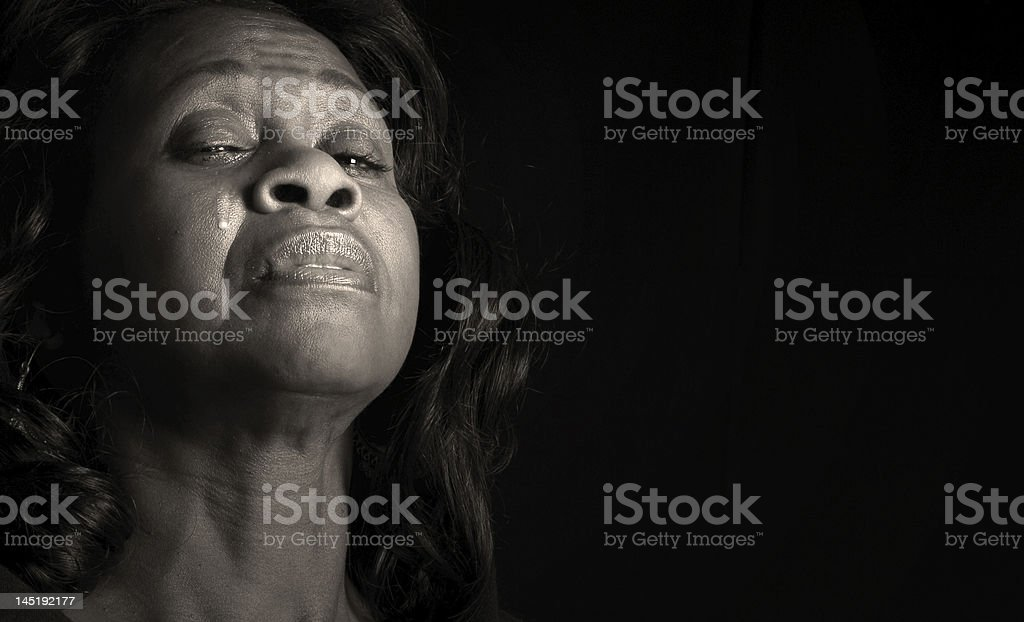 A woman with a long hair crying in the dark stock photo