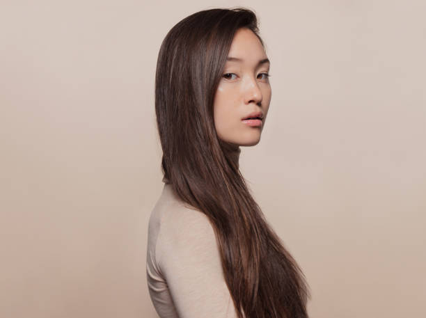Woman with a long straight hair Portrait of beautiful young woman with long brown hair standing against beige background. Asian woman with a long straight hair looking at camera. korean ethnicity stock pictures, royalty-free photos & images