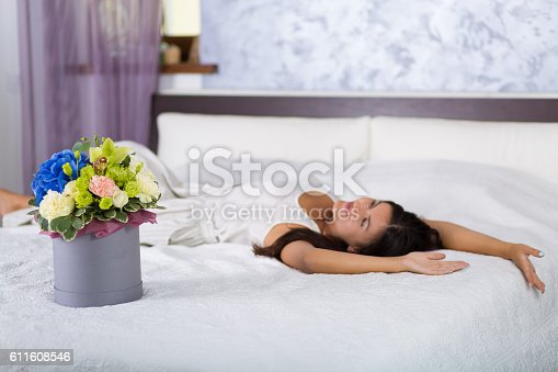 istock Woman with a lovely hat box with flowers 611608546