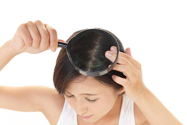 Woman with a magnifying glass Woman taking care of her hair human scalp stock pictures, royalty-free photos & images