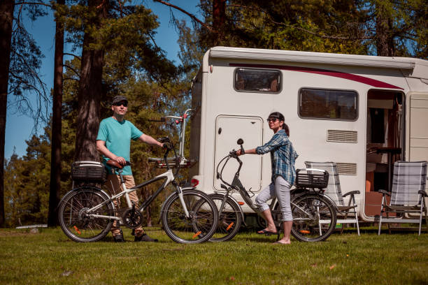 Woman with a man on electric bike resting at the campsite. Woman with a man on electric bike resting at the campsite. Family vacation travel, holiday trip in motorhome RV, Caravan car Vacation. rv bike stock pictures, royalty-free photos & images