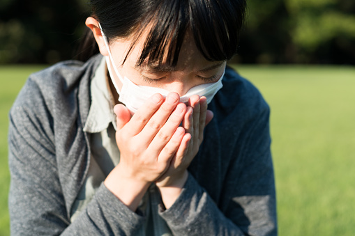 istock Woman with a mask coughing 614718420