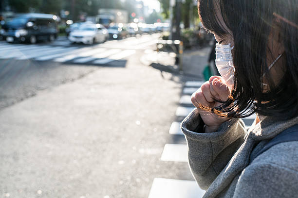 woman with a mask coughing - くしゃみ 日本人 ストックフォトと画像