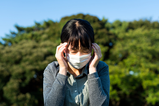 istock Woman with a mask feeling sick 614718602