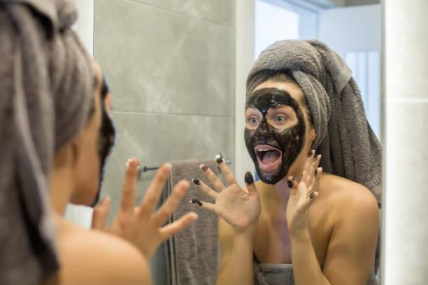 vrouw met een masker op zoek spiegel - mirror mask stockfoto's en -beelden