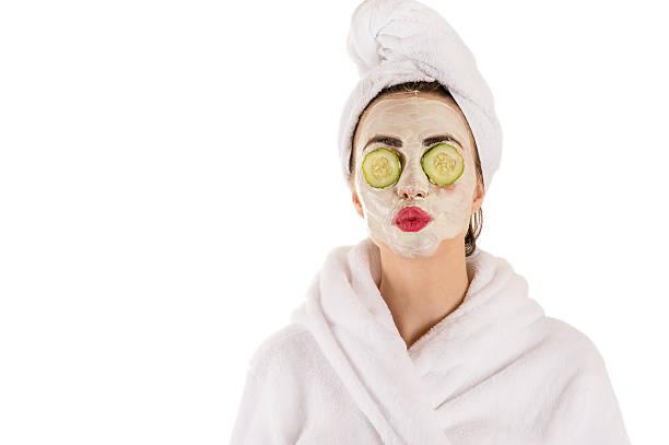 frau mit einer maske im gesicht wellness - gurkenmaske stock-fotos und bilder