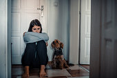istock Woman With A Mental Problems Is Sitting Exhausted On The Floor With Her Dog Next To Her 1277237827