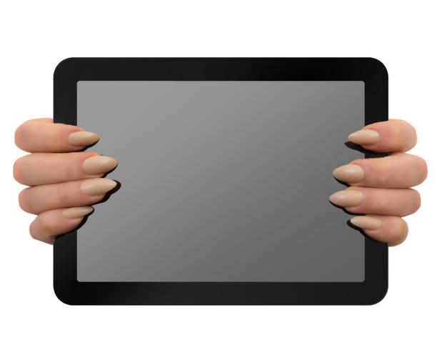 frau mit einem nackten farbigen stiletto maniküre hält tablet mit beschneidungspfad - nails stiletto stock-fotos und bilder